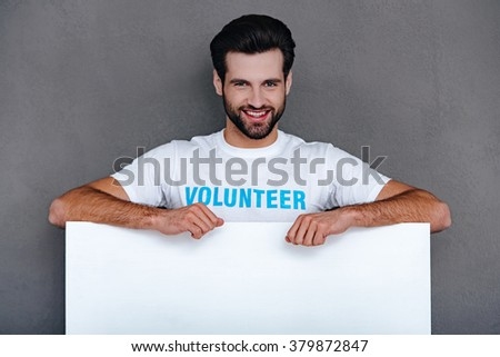 Please donate! Confident young man in volunteer t-shirt leaning to white board and looking at camera with smile while standing against grey background