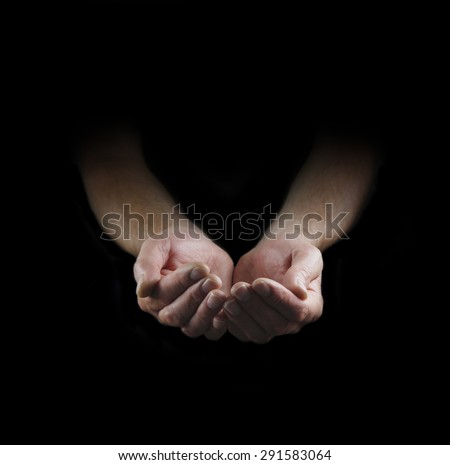 Please Help -  Man's cupped hands emerging from darkness with plenty of copy space around - stock photo