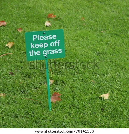 Please keep off the grass sign in a meadow