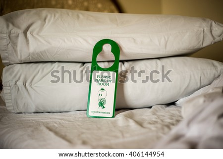 Please Make Up Room sign on an untidy bed - stock photo