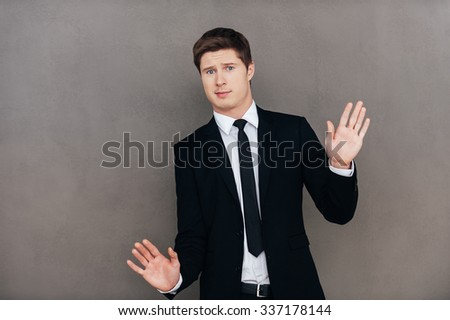 Please no! Frustrated young man in formalwear stretching out hands and looking at camera while standing against grey background