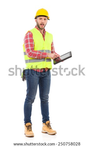 Please read the instruction. Manual worker in yellow helmet and lime waistcoat holding a digital tablet and talking. Full length studio shot isolated on white.