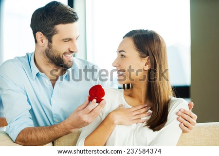 Please say yes! Handsome young man making a proposal while giving an engagement ring to his girlfriend  - stock photo