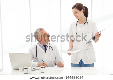 Please, sign here. Two medical colleagues looking at each other and smiling while signing the documents
