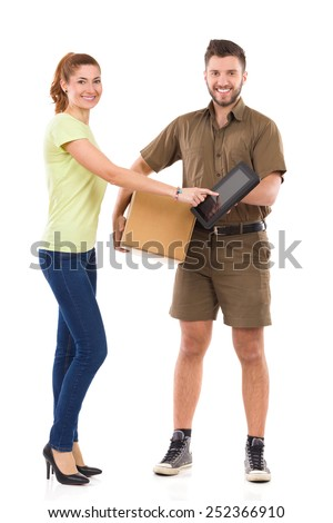 Please sign here. Woman receives a package and pointing at courier's digital tablet. Full length studio shot isolated on white. - stock photo