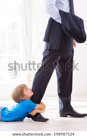Please stay! Sad little boy embracing his father leg and looking up while lying on the floor  - stock photo