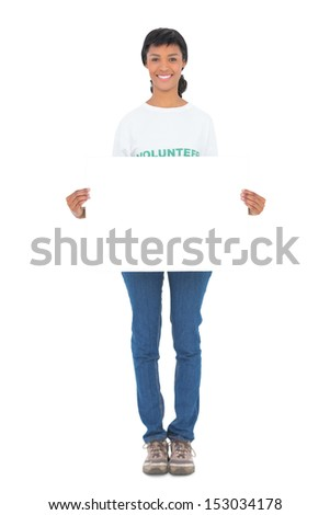 Pleased black haired volunteer holding a white panel in front of camera on white background - stock photo
