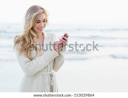 Pleased blonde woman in wool cardigan using a mobile phone on the beach - stock photo