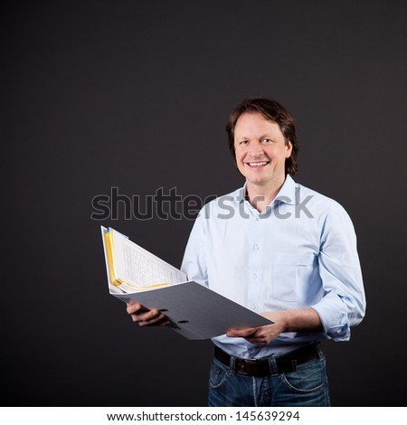 pleased business man looking up from folder against black - stock photo