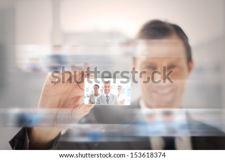 Pleased businessman presenting a picture of a business team on digital screen - stock photo
