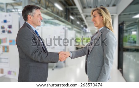 Pleased businessman shaking the hand of content businesswoman against college hallway - stock photo