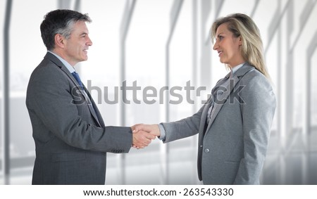 Pleased businessman shaking the hand of content businesswoman against room with large window looking on city