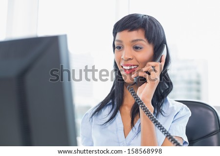 Pleased businesswoman answering the telephone in office - stock photo