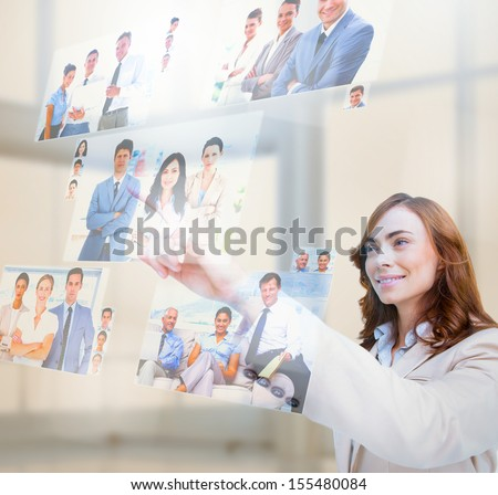 Pleased businesswoman selecting pictures on digital screen - stock photo