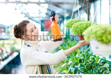 Pleased pretty young woman gardener spraying flowers and plants in greenhouse - stock photo