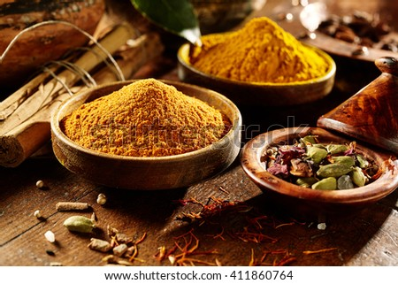 Pleasingly lit wooden table with ground and whole curry powder and turmeric in bowls beside hard bamboo sticks - stock photo
