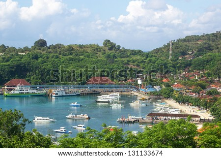 Pleasure boats and luxury yachts moored in a sheltered bay with a resort or village nestling amongst the palms lining its shores and people enjoying the sandy beach - stock photo