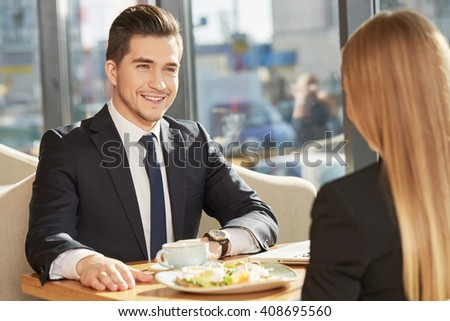 Pleasure to work with you. Cheerful businessman smiling joyfully having a business meeting with his female colleague at the restaurant - stock photo