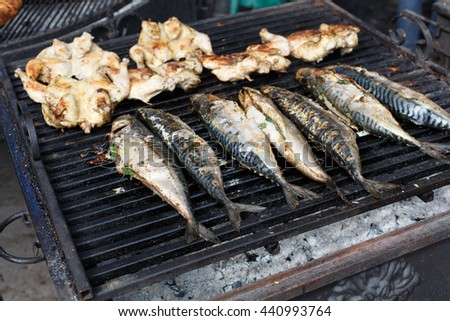 Plenty of chicken tabaka and fish grilled at barbecue. Mackerel bbq outdoors at picnic, party. Street food, roasted meat and seafood grill takeaway at grate - stock photo