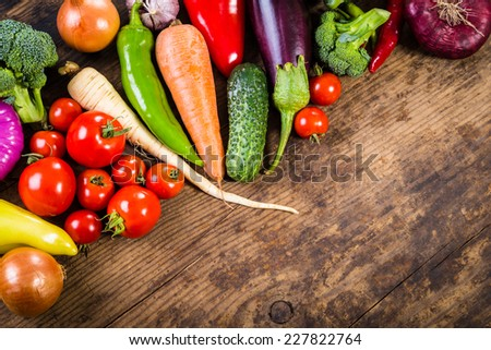Plenty of colorful vegetables on brown wooden background - stock photo