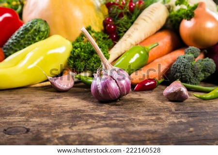 Plenty of colorful vegetables on old wooden table - stock photo