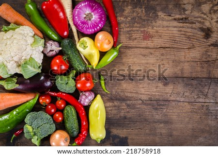 Plenty of colorful vegetables on wooden background - stock photo