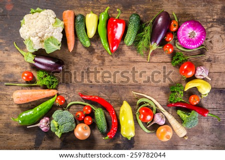 Plenty of colorful vegetables on wooden background with copy space - stock photo