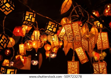 Plenty of lanterns hanging from the ceiling at the fairground in the pitch-black darkness