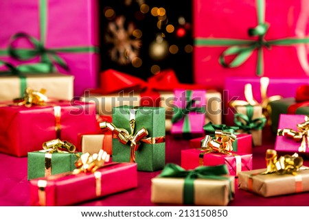 Plenty of single-colored Christmas presents placed on a red, smooth cloth. Vibrant colors. Narrow depth of field. Blurred baubles and stars over pitch black background. Most gifts in soft focus.  - stock photo