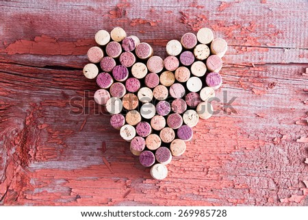 Plenty of Wine Bottle Corks Formed in Heart Shape for Love Concept on Top of an Old Wooden Table in High Angle View. - stock photo