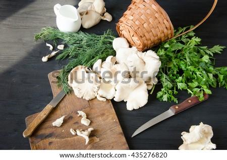 pleurotus black wooden table wicker with herbs - stock photo