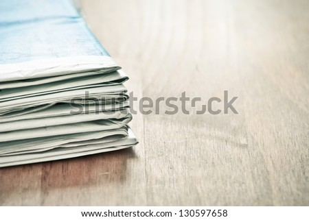 Plie of folded newspapers on a wooden surface - stock photo