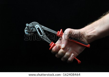 Pliers and a Hand on a Black Background