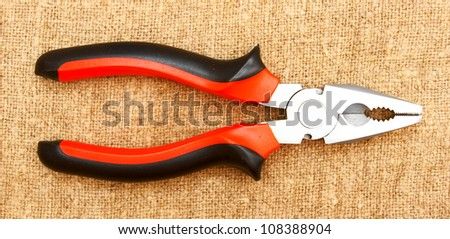 Pliers on a fabric . - stock photo