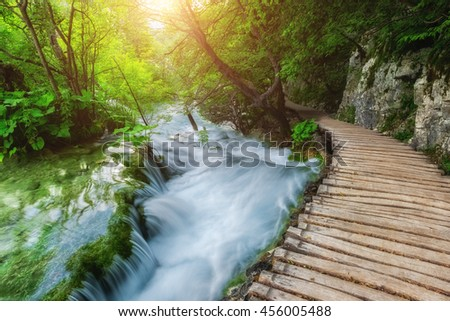 Plitvice Lakes National Park, tourist route on the wooden flooring along the stream, Croatia, nature sunny background - stock photo