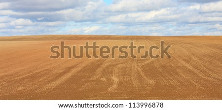 Ploughed and seeded field. Autumn natural background. - stock photo