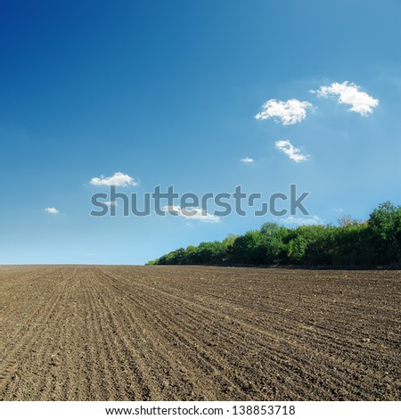 ploughed field in spring and blue sky - stock photo