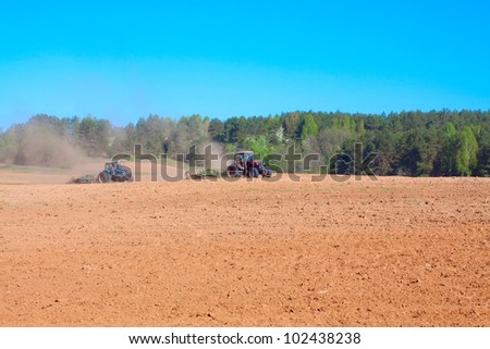 Ploughing tractor during cultivation agriculture works at field with plough - stock photo