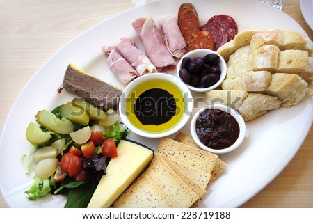 Ploughmans Lunch antipasto style platter including, crusty bread, cheese, cold meat, ham, olives, olive oil and balsamic vinegar, crackers, pate and salad. - stock photo