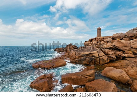 Ploumanac'h lighthouse against blue cloudy sky. It is an active lighthouse in Cotes-d'Armor, France, located in Perros-Guirec. The structure is composed of pink granite. - stock photo