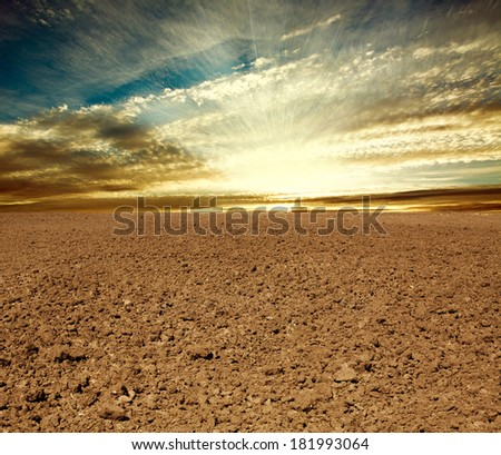 Plowed farmland field on the background of cloudy sky in sunset rays - stock photo