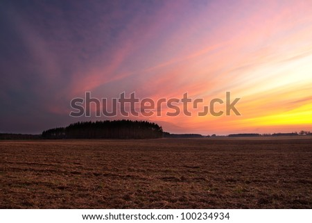 Plowed field after sunset - stock photo