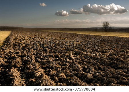 Plowed field at winter time - stock photo