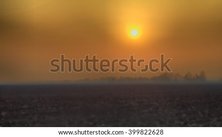 plowed field. Backlight shooting at the rising sun - stock photo