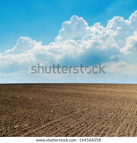 plowed field in spring and clouds over it