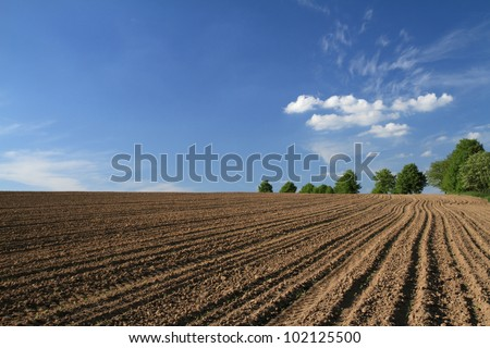 Plowed field in spring time with blue sky. - stock photo