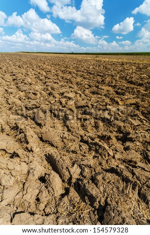 Plowed field under blue cloudy sky, vertical image, Poland, Europe