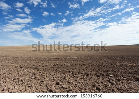 Plowed field with blue sky and beautiful clouds