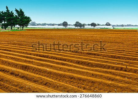 Plowed Fields on the Background of Greenhouse in Italy - stock photo