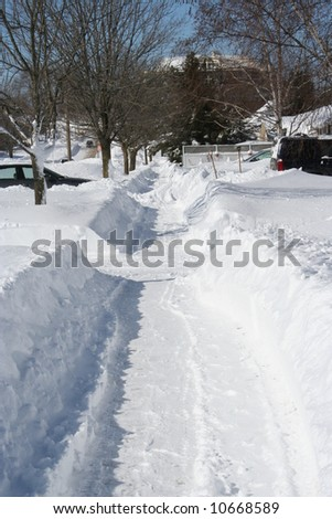 Plowed sidewalk after a heavy snowstorm - stock photo